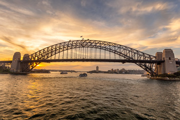 View of Sydney harbor bridge at sunset and a boat sailing in the background © Sergey