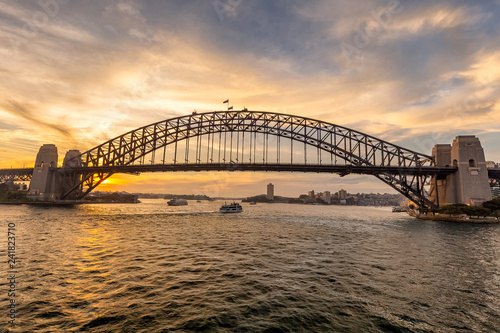 View of Sydney harbor bridge at sunset and a boat sailing in the background
