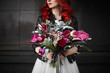 Fashionable and beautiful model girl with red hair and bright makeup, in a white wedding dress and in a leather jacket, with a big and luxury bouquet of exotic flowers in her hands, posing outdoors