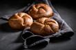 Leinwanddruck Bild - Closeup of tasty golden buns on dark grey concrete