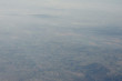 view from the window of the plane to the ground with mountains, rivers and horizon in the clouds and fog - 241832977