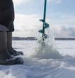 Leinwanddruck Bild - Man catches fish on ice in winter