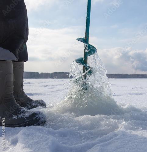 Leinwanddruck Bild Man catches fish on ice in winter