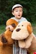 Boy child with big plush toy dogs expressing joyful surprise