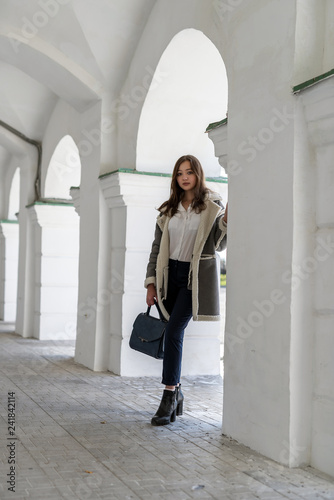 A girl in a light sheepskin coat at the colonnade