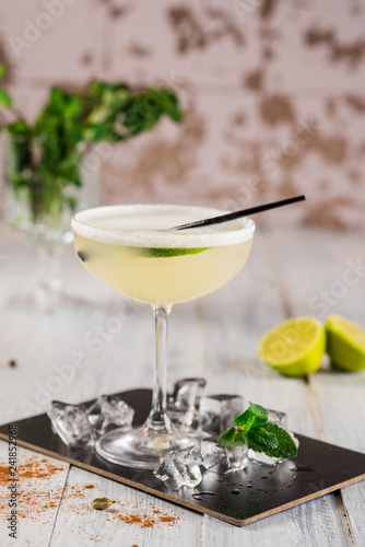 An alcohol cocktail with lime in glass on white background