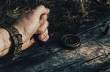 Man dirty hand holds a knife, a compass on an old log in forest.Survival. - 241856916