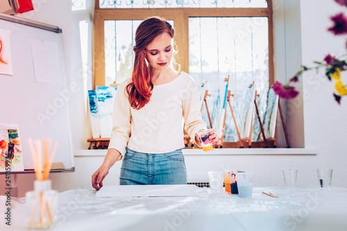 Art teacher wearing jeans and beige shirt standing in painting studio