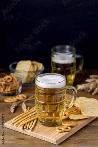 Glass Mug of Tasty Light Beer and Snacks on Wooden Table Pretzel Cracker with Solt Vertical