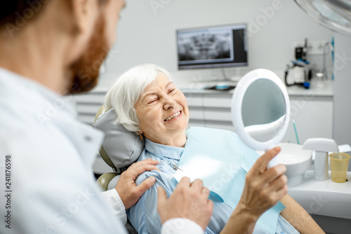 Leinwanddruck Bild Happy elderly woman enjoying her beautiful toothy smile looking to the mirror in the dental office
