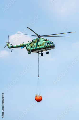 Green firefighting helicopter transporting water.