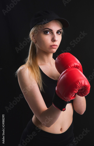 Beautiful young girl learns self-defense techniques in red Boxing gloves, black top and shorts