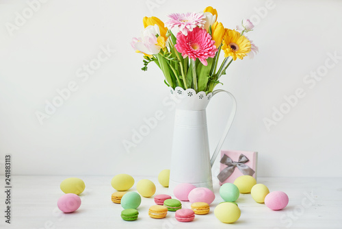 Easter cake, eggs and rabbits with fresh flowers on the table, the kitchen is decorated for Easter