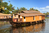 A traditional house boat is anchored on the shores of a fishing lake in Kerala's Backwaters, India. - Image