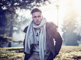 One handsome blue eyed young man in urban setting in European city park