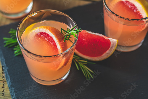 Leinwanddruck Bild Pink cocktail with grapefruit, ice and rosemary
