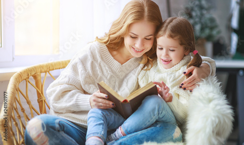 happy family mother reads book to child to daughter by window