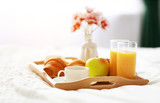 breakfast in bed of coffee, croissants, orange juice and fruit on tray - 241911554
