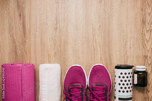 Foto Murales Sport flat lay with sneakers yoga mat on wooden floor background,Sport top view concept.