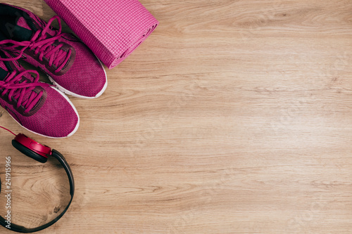 Sport flat lay with sneakers yoga mat and headphone on wooden floor background,Sport top view concept.