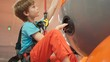 Boy doing indoor climbing wall challenge at trampoline park