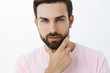 Leinwandbild Motiv Headshot of handsome cheeky and sensual sexy european man with beard and blue eyes squinting with desire and seduction gaze touching jawline, looking at camera confident and self-assured