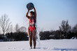 woman pours herself with cold water on the street in winter