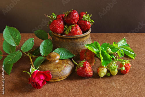Strawberries in a wooden pot and a red rose on a brown tablecloth
