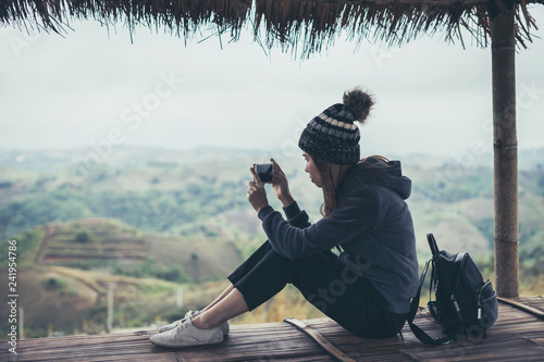 Young woman traveler using smart phone to taking photo