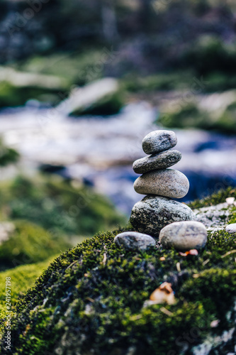 Balancing rock art. Stones balanced on top of each other on the stone with moss. Green color, flowing creek and a stone man. Zen stones or zen stack in the forest next to a river. - 241957198