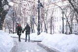 Fototapeta Miasto - Young couple walking through the winter © alexkich