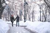 Fototapeta Fototapety miasto - Young couple walking through the winter © alexkich