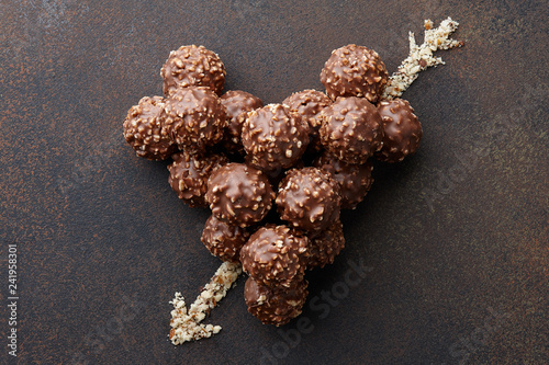 obraz lub plakat Heart shape with arrow made from chocolate truffle candies with hazelnuts and nut crumb on brown textured background, top view