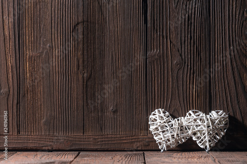 Leinwandbild Motiv Wicker hearts on wooden background