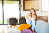 Young woman relaxing on sofa early morning - 241964340
