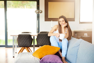 Young woman relaxing on sofa early morning