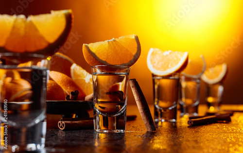 Glasses of tequila with orange and cinnamon sticks.