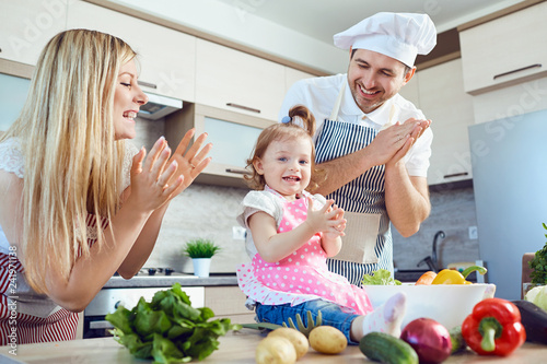 A family prepares food from vegetables in the kitchen. - 241971138