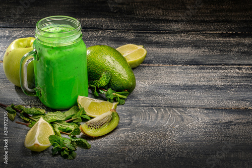 Foto Murales Healthy green vegetables smoothie in the jar on rustic wooden background