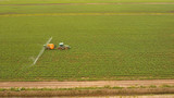 Aerial view tractor spraying chemicals on large green field. Spraying the herbicides on the farm land. Treatment of crops against weeds. - 241975741