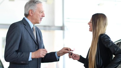 Portrait of a car salesman giving car keys to young woman standing next to white shiny luxury car in dealership showroom © Minerva Studio