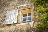 Very old and weathered window with shutter surrounded by orange trumpet flowers in the Mediterranean masonry facade of an old French house. - 241980149