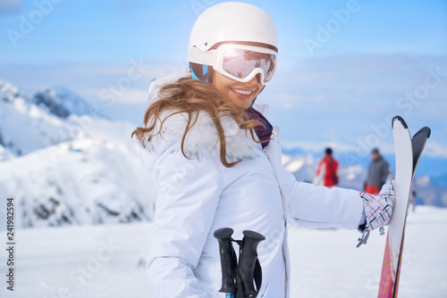 woman skier close up portrait wearing white healmet with mask in snow winter mountain © ZoomTeam