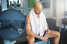 "Постер, картина, фотообои ""Sporty man relaxing in the gym and drinking a bottle of water"""
