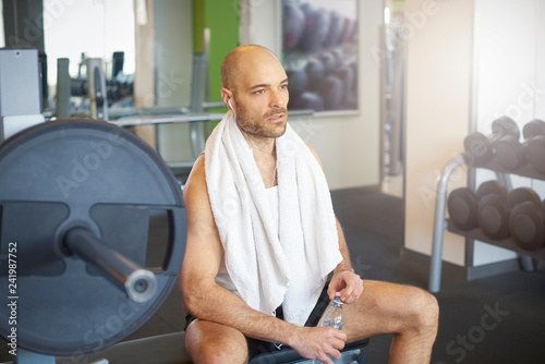 Poster Sporty man relaxing in the gym and drinking a bottle of water