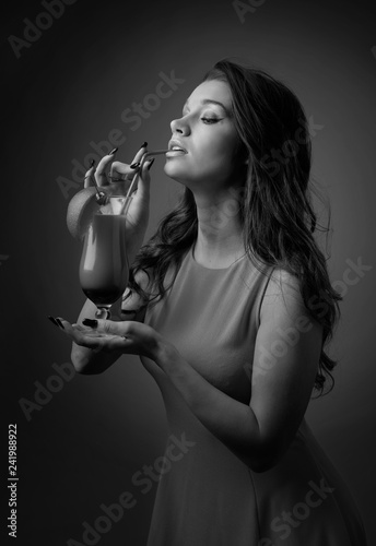 Young beautiful girl with glass of cocktail.