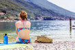Beautiful young woman in bikini is sitting on the pebble beach and enjoying the view, vacation in italy