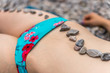 Quadro Pebble stones on the body of a young attractive woman, wellness