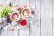 Leinwandbild Motiv Girl hands hold hot chocolate with marshmallow hearts, red pink white color with chocolate pieces, sugar sprinkles, old wooden background copy space top view, hands in pictute flatlay