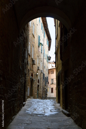 Narrow alley in italian old town seen through the arch - 241996744